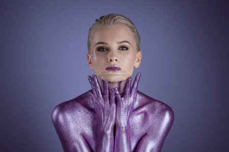 attractive fashionable woman painted with purple glitter, isolated on violet