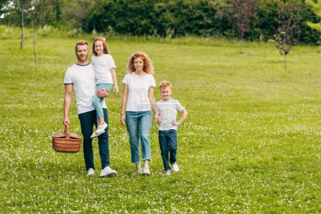 happy family smiling at camera while walking with picnic basket in park