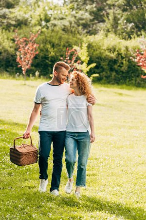 happy young couple with picnic basket walking on lawn at park