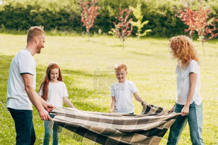 happy family with two kids holding plaid while spending time together at picnic in park