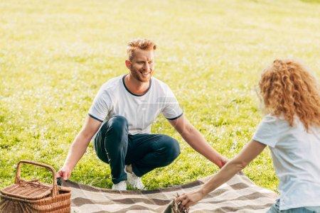 Foto de Pareja pelirroja feliz celebración de plaid y mirando el uno al otro picnic en el Parque - Imagen libre de derechos