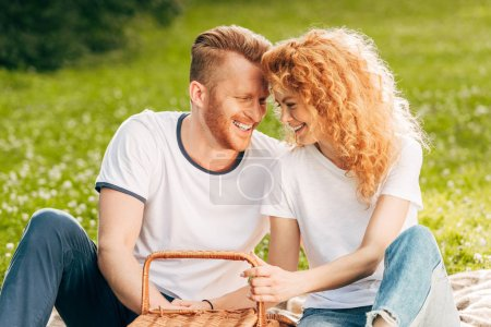 happy redhead couple holding basket while sitting at picnic in park