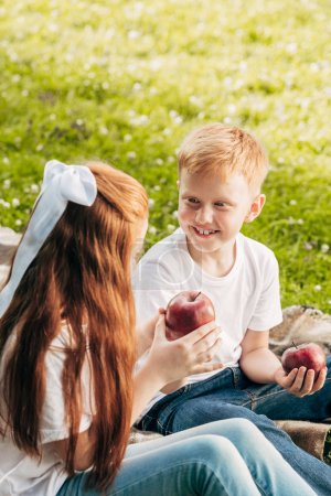 happy redhead kids eating apples while sitting at picnic in park
