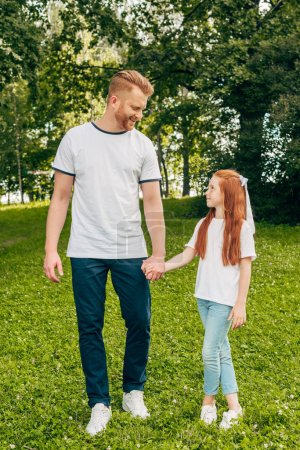 happy red haired father and daughter holding hands and smiling each other in park