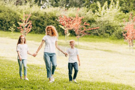 happy mother with two children holding hands and walking at park