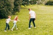father with cute little kids playing with soccer ball in park
