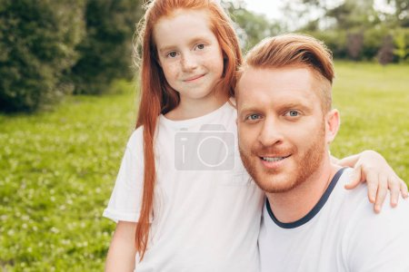 happy redhead father and daughter smiling at camera in park
