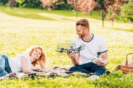 glückliches Rotschopf-Paar spielt mit Drohne bei Picknick im Park