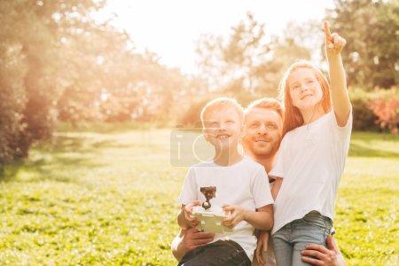 Photo pour Heureux père avec mignon petits enfants jouer avec drone ensemble au parc - image libre de droit