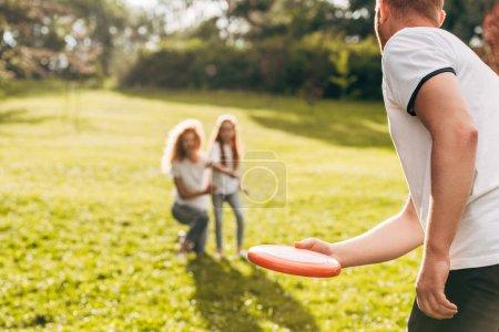 Photo pour Recadrée tir de père jetant disque volant à la mère et la fille dans le parc - image libre de droit