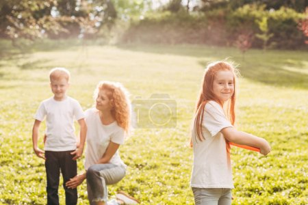 happy child playing with flying disk while mother and brother resting behind in park