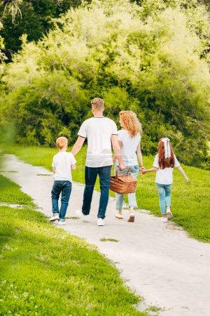 Photo pour Vue arrière du famille avec pique-nique panier marchons ensemble dans le parc - image libre de droit