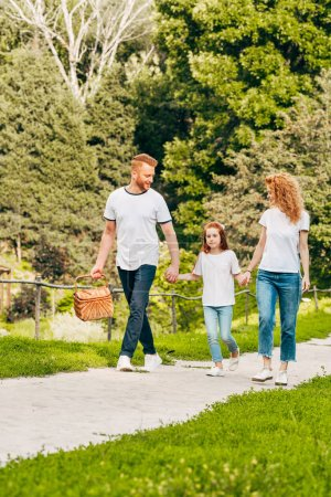 happy family holding hands and walking at picnic in park