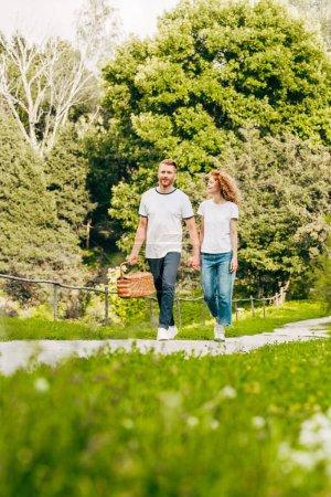 Foto de Jóvenes felices pareja con cesta de picnic en el hermoso parque - Imagen libre de derechos