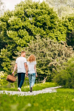 back view of young couple with picnic basket walking in beautiful park
