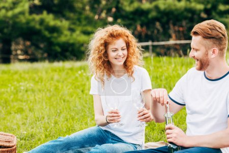happy couple opening bottle of wine at picnic in park