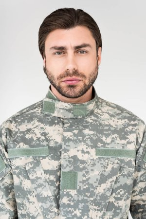 portrait of confident bearded soldier in military uniform looking at camera isolated on grey
