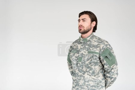 side view of confident bearded soldier in military uniform looking away on grey backdrop