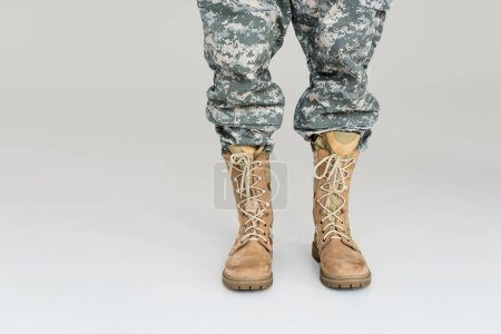cropped shot of soldier in military uniform and boots isolated on grey