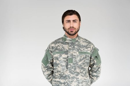 portrait of confident bearded soldier in military uniform on grey backdrop