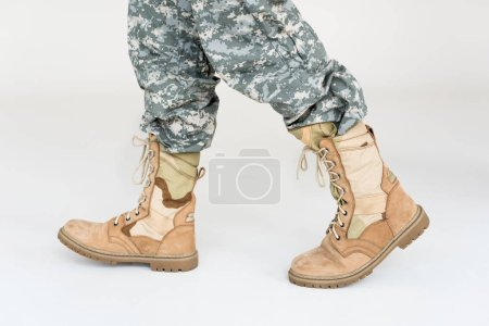 partial view of male soldier in camouflage clothing and boots on grey background