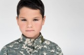 portrait of kid in military uniform looking at camera on grey background