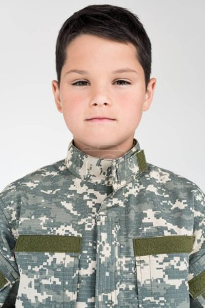 portrait of little kid in military uniform looking at camera on grey background