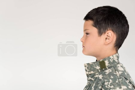 side view of kid in military uniform looking away on grey background