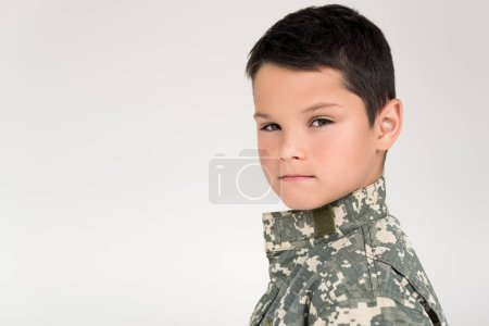 side view of kid in military uniform looking at camera on grey background