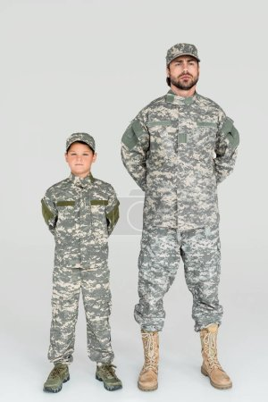 father and son in military uniforms looking at camera on grey background