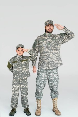 father and son in military uniforms saluting and looking at camera on grey background