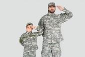 """Постер, картина, фотообои """"Портрет уверенно солдат и сына в военную форму, салютование изолированные на серый"""""""
