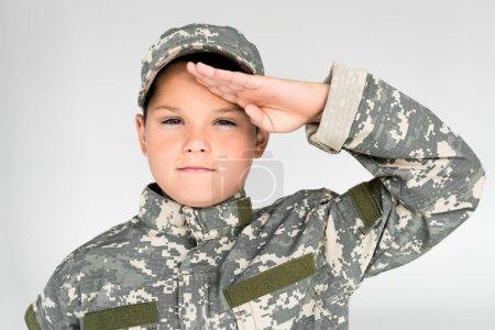 Photo pour Portrait d'enfant en uniforme militaire, regardant la caméra et saluant sur fond gris - image libre de droit