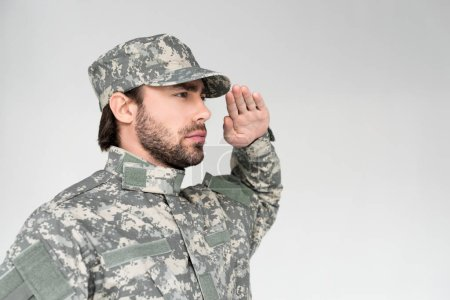 side view of confident bearded soldier in military uniform saluting on grey background