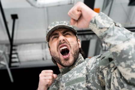 low angle view of emotional soldier in military uniform with blurred backdrop