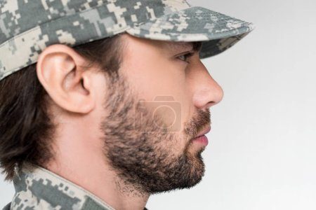 side view of confident bearded soldier in military uniform looking away isolated on grey