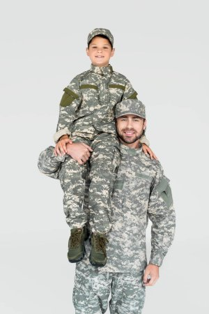 smiling soldier holding son in military uniform on shoulder isolated on grey