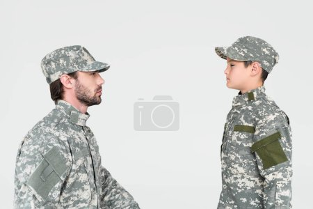 side view of soldier and son in military uniforms looking at each other isolated on grey