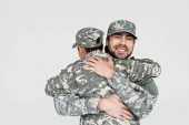partial view of smiling soldier and son in military uniforms hugging each other isolated on grey