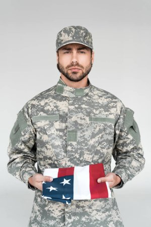 portrait of male soldier in military uniform with american flag in hands on grey backdrop