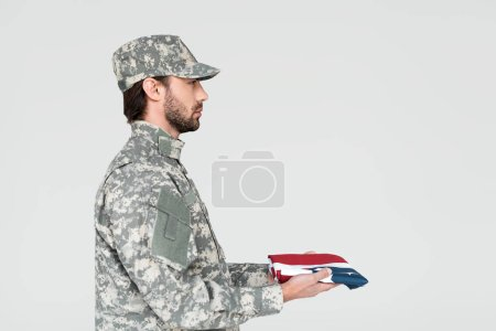 side view of male soldier in military uniform with american flag in hands on grey backdrop