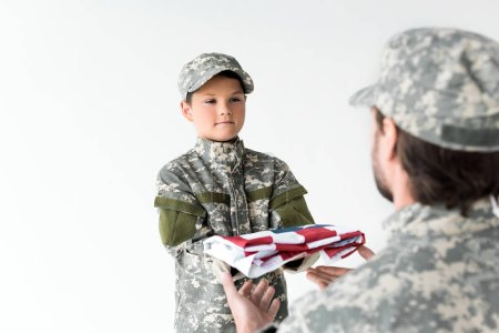 partial view of little boy in camouflage clothing giving folded american flag to soldier on grey background