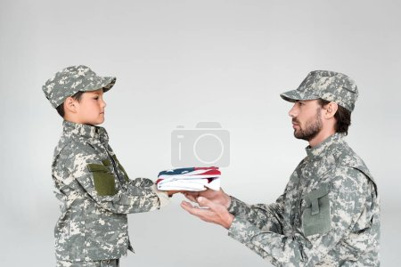 side view of little boy in camouflage clothing giving folded american flag to soldier on grey background