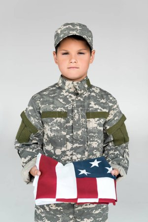 portrait of kid in military uniform holding folded american flag isolated on grey