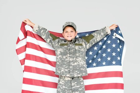 portrait of cheerful kid in military uniform with american flag isolated on grey