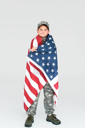 boy in military uniform covered with american flag looking at camera on grey background