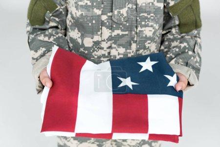 Photo pour Plan recadré d'un enfant en uniforme militaire tenant un drapeau américain plié dans des mains isolées sur du gris - image libre de droit