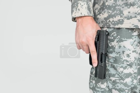 cropped shot of male soldier in military uniform holding gun isolated on grey