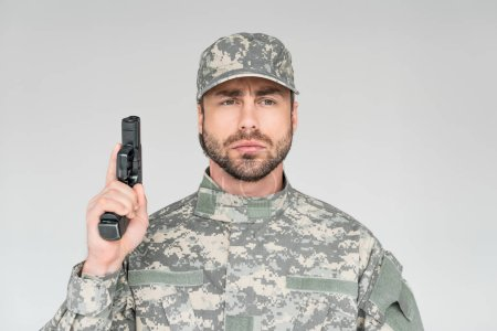 portrait of male soldier in military uniform holding gun isolated on grey