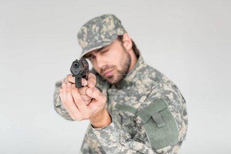 Photo pour Foyer sélectif du soldat masculin en uniforme militaire tenant le pistolet isolé sur gris - image libre de droit